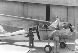 1955 Oct - Mary Carmel under wing as Tom's plane gets serviced in front of hanger in Little Rock, AR